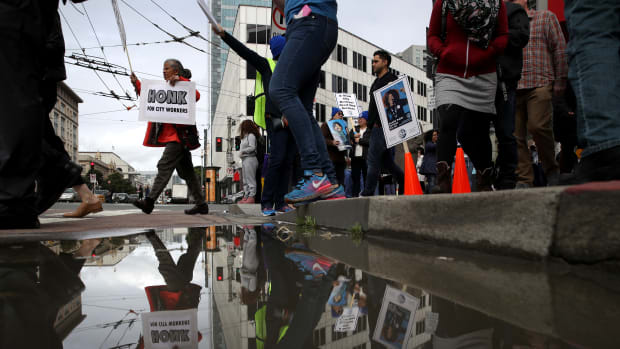 A San Francisco city worker holds a sign as workers march during a rally outside of the City and County of San Francisco Human Resources office on March 7th, 2019, in San Francisco, California. Hundreds of San Francisco city workers staged a rally to demand a fair contract that addresses pay equity for women.