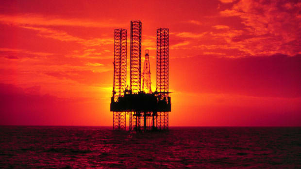 An offshore oil rig is pictured at sunset.