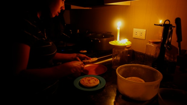 On March 12th, 2019, a woman cooks dinner at her house during a blackout, which affects the water pumps, in Caracas, Venezuela. Over 70 percent of the country was in darkness amid an ongoing political dispute between President Nicolas Maduro and Juan Guaido, who has been declared interim president by the national assembly.