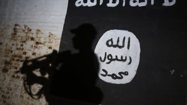 A member of the Iraqi forces walks past a mural bearing the logo of the Islamic State group in a tunnel.