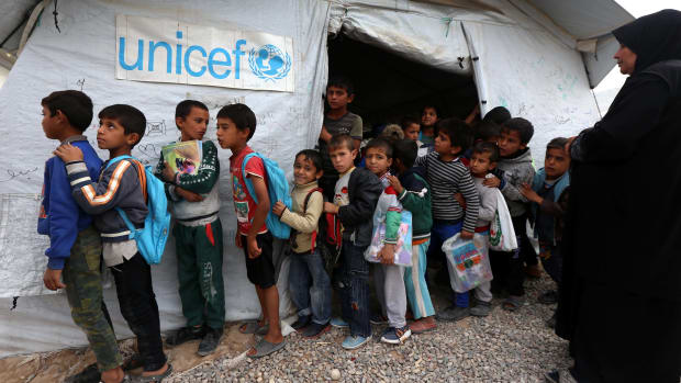 Displaced Iraqi children from the former embattled city of Mosul line up outside a UNICEF school.