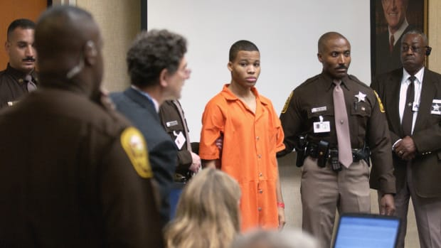 Sniper suspect Lee Boyd Malvo (center) is escorted by deputies as he is brought into court to be identified by a witness during the murder trial in courtroom 10 at the Virginia Beach Circuit Court on October 22nd, 2003, in Virginia Beach, Virginia.