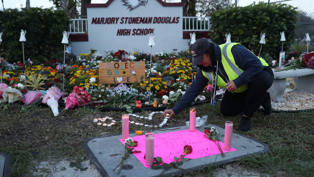 Wendy Behrend, a school crossing guard who was on duty when a shooter opened fire in Marjory Stoneman Douglas High School in Parkland, Florida, pays her respects at a memorial one year after the shooting.