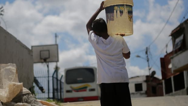 A child carries a container filled with water at the slum of Petare, on April 4th, 2019, in Caracas, Venezuela. Since March 7th, Venezuela has been suffering intermittent blackouts, which have affected the water supply. People have to collect water from waterfalls and pipes and carry it to their homes. This water, not always suitable for human consumption, is used for drinking, cooking, and bathing.