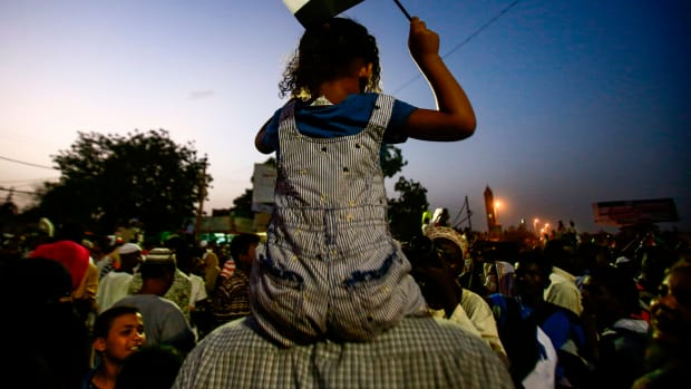 A Sudanese child waves a national flag as she sits atop the shoulders of a man during a late demonstration outside the army headquarters in the Sudanese capital Khartoum on April 12th, 2019. Protesters defied a night-time curfew to keep up four months of mass demonstrations.