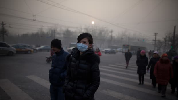 A woman wearing a mask crosses a road during severe pollution in Beijing on January 12th, 2013.