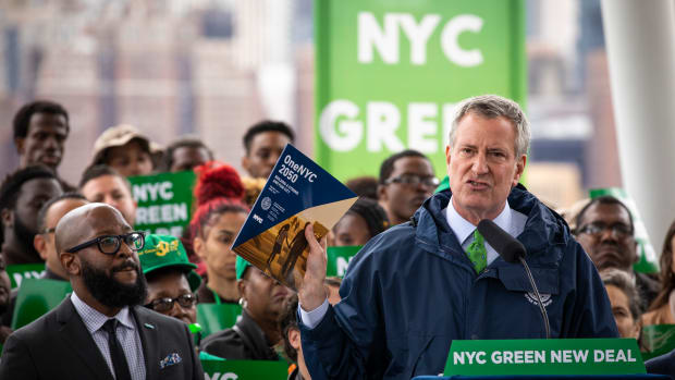 New York City Mayor Bill de Blasio holds up a copy of One NYC 2050 as he speaks the city's response to climate change at Hunters Point South Park on April 22nd, 2019.