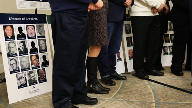 Survivors of sexual abuse by priests and clergy stand before photos of accused religious men during a news conference with lawyer Jeff Anderson of Jeff Anderson & Associates on February 14th, 2019, in New York City.