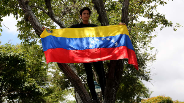 A student standing in a tree displays a Venezuelan flag during a rally in support of opposition leader Juan Guaidó and against Nicolás Maduro at Universidad Central de Venezuela on May 2nd, 2019, in Caracas, Venezuela. After two days of violent clashes between pro-Guaidó and pro-Maduro groups including civilian, police, and military forces that resulted in four dead and over 100 wounded, Venezuelans supporting Guaidó are taking to the streets and responding to the call for strikes.