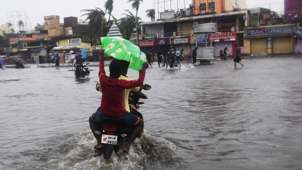 Indian residents ride on a bike along a flooded road after Cyclone Fani landfall in Puri, in the eastern Indian state of Odisha, on May 3rd, 2019.