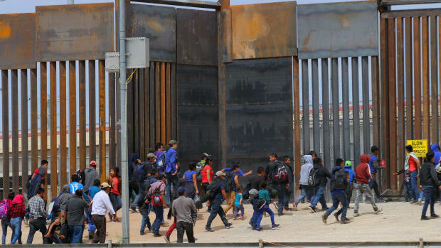 Central American migrants walk as they are detained by U.S. Customs and Border Patrol agents at the border wall in Ciudad Juarez, Chihuahua state, Mexico, on May 7th, 2019.