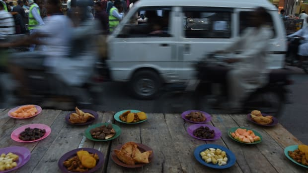Pakistani commuters ride past plates of Iftar food placed for residents to break their fast along a street in Karachi, Pakistan, on May 9th, 2019.