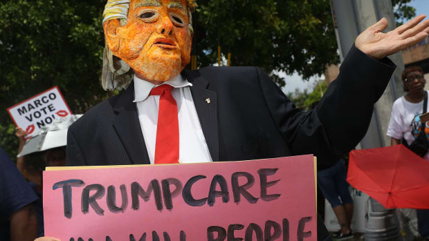 A man dressed as Donald Trump at a Florida protest against the Senate's 2017 health-care bill, which proposed drastic Medicaid cuts.