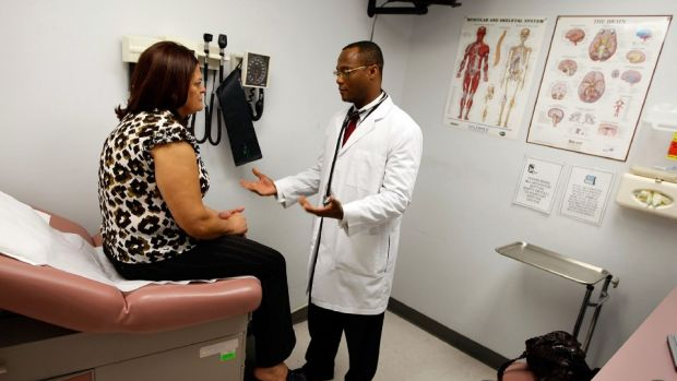 Photo showing a doctor talking to a patient sitting on a bed in an exam room