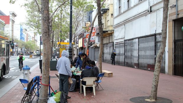 People play chess in the early evening along Market St. in the Tenderloin neighborhood of San Francisco, California.