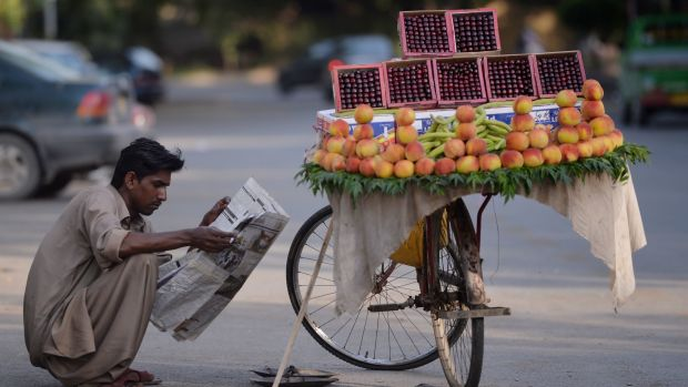 A fruit vendor reads a newspaper as he waits for customers on a street in Islamabad, Pakistan, on May 23rd, 2017.
