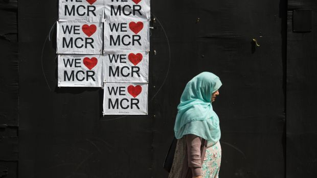 A woman walks past a poster displaying a message of defiance after the terror attack of May 22nd in Manchester, England, on May 31st, 2017.