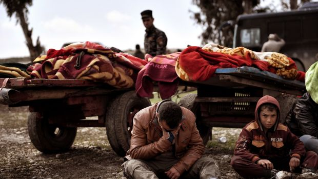 Relatives mourn as bodies of Iraqi residents of west Mosul killed in an airstrike are placed and covered with blankets on carts on March 17th, 2017.