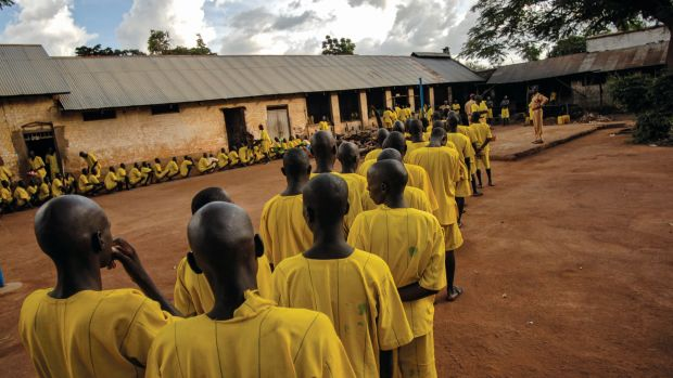 Prisoners, many of whom claim to be juveniles, line up for dinner at Lira Prison, Poor birth records make it difficult for Ugandan prison officials to remove younger prisoners from adult facilities.