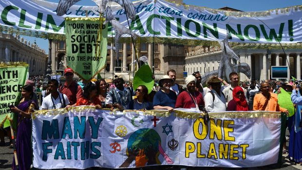 Activists display banners calling for action on climate change and against world poverty as they arrive on St. Peter's Square prior to Pope Francis' Sunday Angelus prayer at the Vatican.