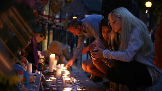 People light candles as they observe a vigil outside Notting Hill Methodist Church following the blaze at Grenfell Tower, a residential tower block in west London on June 15th, 2017.