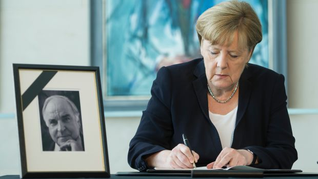 German Chancellor Angela Merkel writes in a condolences book for former chancellor Helmut Kohl on June 18th, 2017, in Berlin, Germany.