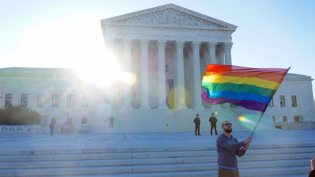 A student waves a Pride flag,