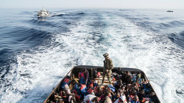 A Libyan coast guardsman stands on a boat during the rescue of 147 undocumented immigrants attempting to reach Europe off the coastal town of Zawiyah, 45 kilometers west of the capital Tripoli, on June 27th, 2017. More than 8,000 migrants have been rescued in waters off Libya during the past 48 hours in difficult weather conditions, Italy's coastguard said.