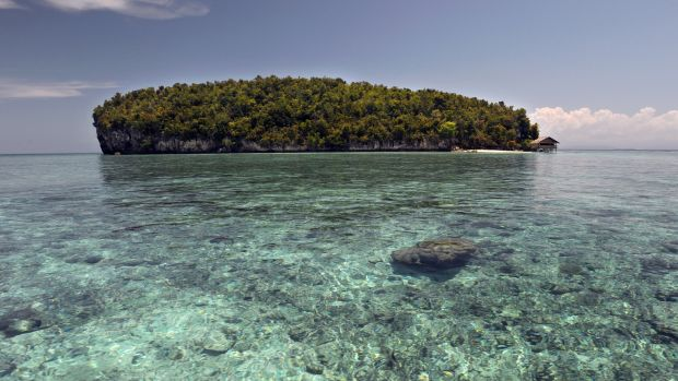 The small island of Koh, surrounded by coral reef in Raja Ampat, located in eastern Indonesia's Papua region.