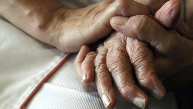 A nurse holds the hands of a person suffering from Alzheimer's disease.