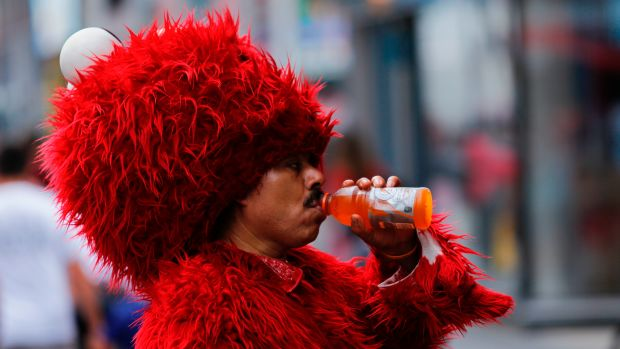 A man dressed as Elmo drinks to keep hydrated at Times Square during a sunny day as hot temperatures continue in New York on July 21st, 2017.