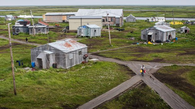 People walk down the elevated, raised wooden sidewalks—created so people don't sink into the melting permafrost—on July 5th, 2015, in Newtok, Alaska. Newtok, which is having to relocate due to melting permafrost and rapid erosion of the river it is established next to, has to have all its fuel and fresh water brought in aboard tankers.