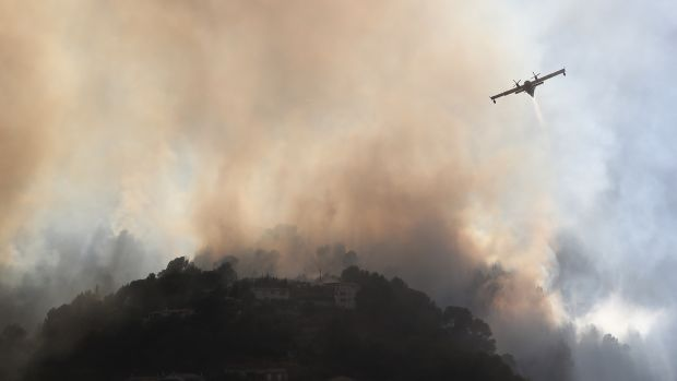 A fire-fighting Canadair aircraft flies to drop water over a fire near Carros, southeastern France, on July 24th, 2017.