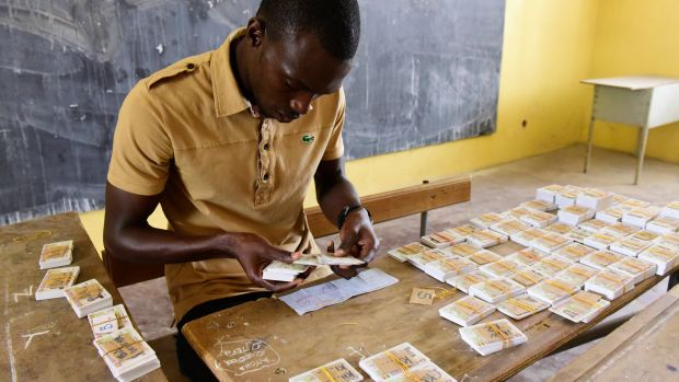 A Senegalese man sorts out voter ID cards in alphabetical order at a school that will be used as a polling station in Dakar on July 26th, 2017, ahead of the country's legislative elections.