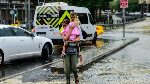 A woman carrying a baby crosses a street during a heavy downpour of rain at Taksim in Istanbul on July 27th, 2017.