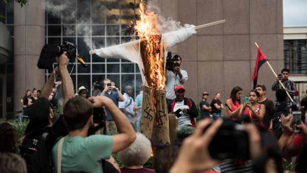 An effigy of U.S. President Donald Trump, dressed in khakis and a white shirt covered in swastikas, is set ablaze during a protest in Minneapolis, Minnesota, on August 14th, 2017.