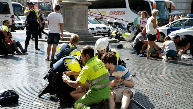 Medics and police tend to injured people near the scene of a terrorist attack in Barcelona, Spain, on August 17th, 2017.