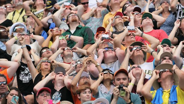 People watch the solar eclipse at Saluki Stadium on the campus of Southern Illinois University on August 21st, 2017, in Carbondale, Illinois. Although much of it was covered by a cloud, with approximately 2 minutes 40 seconds, the area in southern Illinois experienced the longest duration of totality during the eclipse.