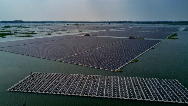A boat tows a group of solar panels before they are connected to a large floating solar farm project on June 14th, 2017, in Huainan, Anhui province, China.