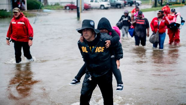 People walk to a Harris County Sheriff air boat while escaping a flooded neighborhood during the aftermath of Hurricane Harvey on August 29th, 2017, in Houston, Texas. Hurricane Harvey has set what forecasters believe is a new rainfall record for the continental United States, officials said Tuesday.
