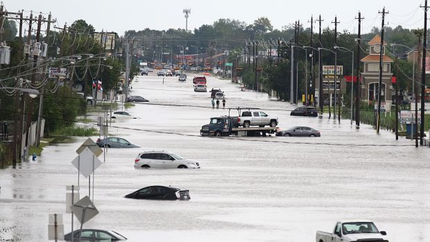 A car gets towed while men walk in the flooded waters of Telephone Road in Houston, Texas, on August 30th, 2017.