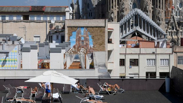 Tourists sunbathe on the terrace of an hotel with the Sagrada Familia in the background in Barcelona, Spain, on September 5th, 2017.