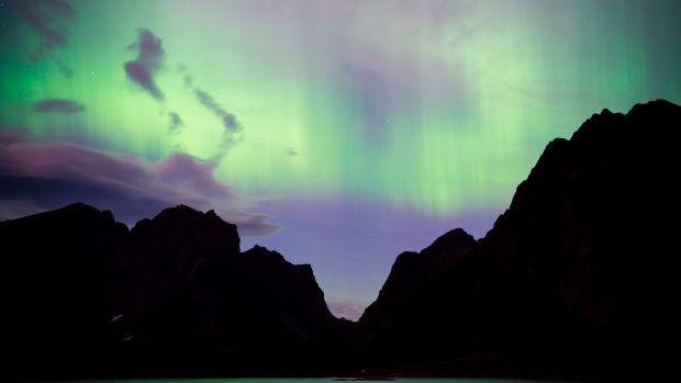 Northern lights (aurora borealis) illuminate the sky over Reinfjorden in Reine, on Lofoten Islands, Arctic Circle, on September 8th, 2017.