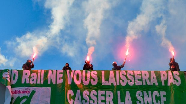 Members of a railway union hold flares during a protest against the reform of the French state-owned railway company SNCF in Paris, France, on March 12th, 2018.