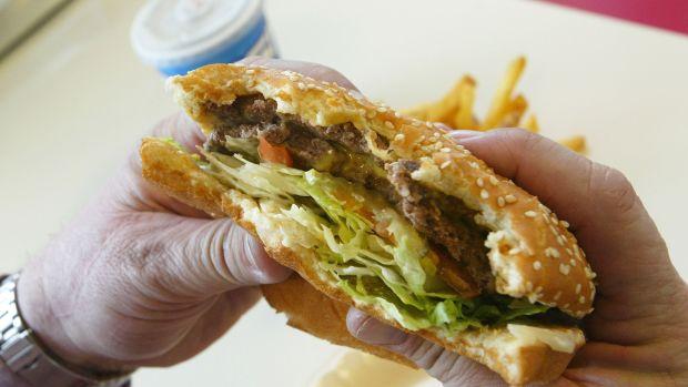 A man prepares to bite into a double cheeseburger at Majors Hamburgers, in Yakima, Washington.