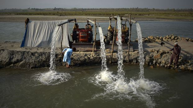 Pakistani farmers use tractors to pump water used to irrigate fields at the Kabul River on the outskirts of Peshawar, Pakistan, on March 22nd, 2018.
