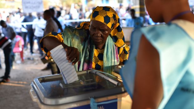 A women cast her ballot as part of the general elections, on March 7th, 2018, at a polling station in Freetown.