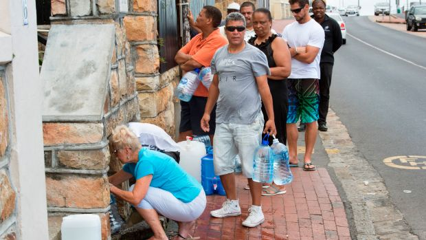People collect drinking water from pipes fed by an underground spring, in St. James, about 25km from Cape Town's city center, on January 19th, 2018.