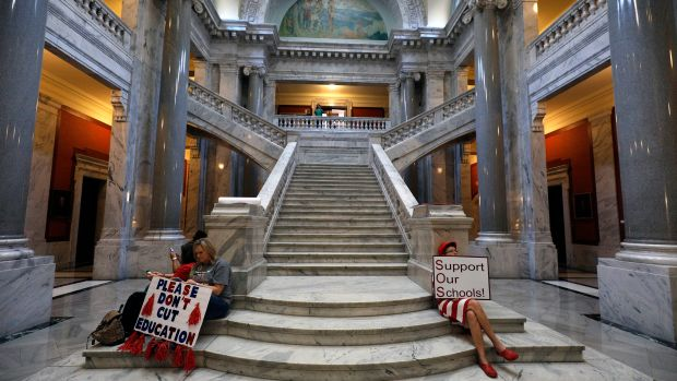 "Kentucky public school teachers sit outside the House chamber as they rally for a ""day of action"" at the Kentucky State Capitol to try to pressure legislators to override Kentucky Governor Matt Bevin's recent veto of the state's tax and budget bills on April 13th, 2018, in Frankfort, Kentucky."