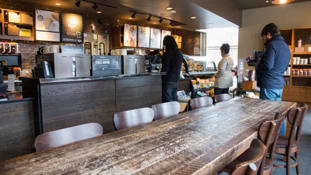 Customers line up inside a Starbucks Coffee shop.